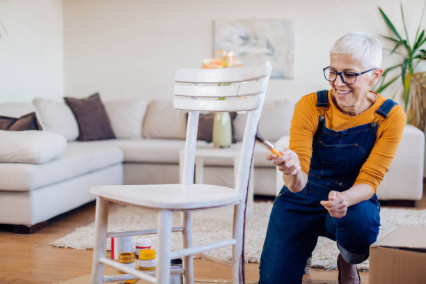 Senior woman coloring an old chair and enjoying at home stock photo