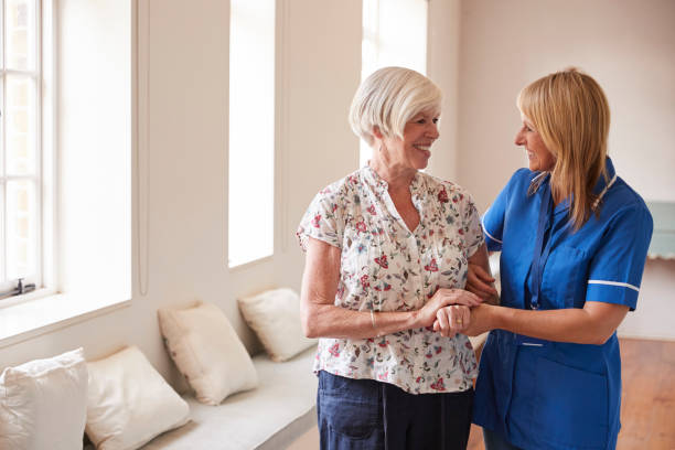 senior woman comforted by nurse at retirement home - take care of your jeans imagens e fotografias de stock