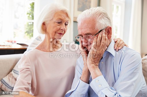 874789476istockphoto Senior Woman Comforting Man With Depression At Home 874788594