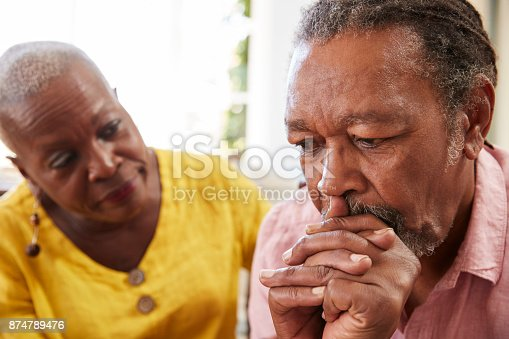 874789476istockphoto Senior Woman Comforting Man With Depression At Home 874789476