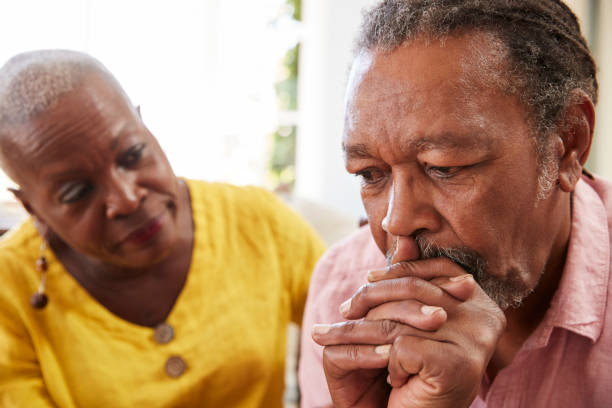 Senior Woman Comforting Man With Depression At Home Senior Woman Comforting Man With Depression At Home husband stock pictures, royalty-free photos & images