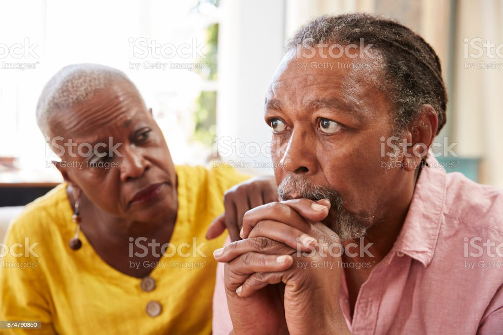 Senior Woman Comforting Man With Depression At Home stock photo
