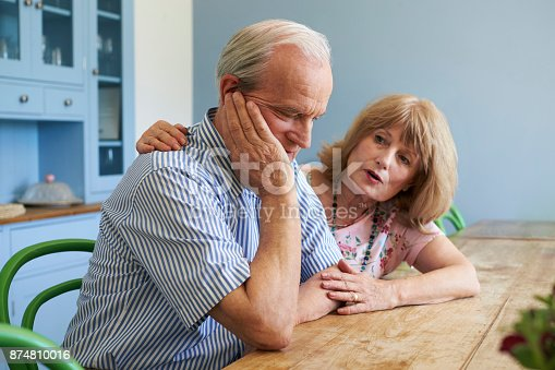 874789476istockphoto Senior Woman Comforting Man With Depression At Home 874810016