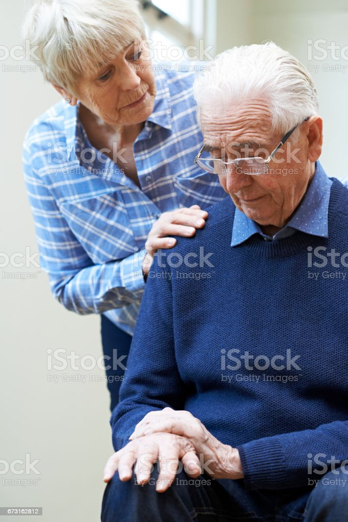 Senior Woman Comforts Husband Suffering With Parkinsons Diesease stock photo