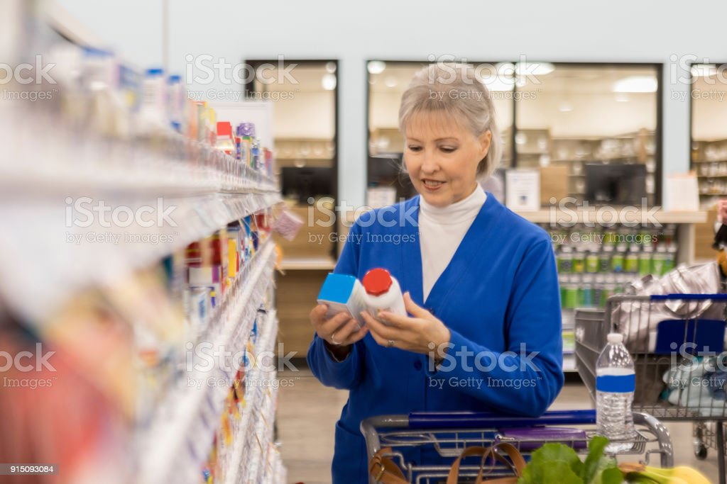 Senior woman compares two over the counter medications stock photo