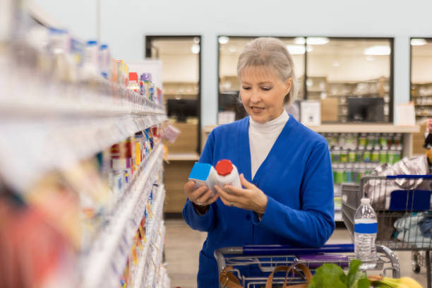 senior woman compares two over the counter medications - vitamin stock pictures, royalty-free photos & images