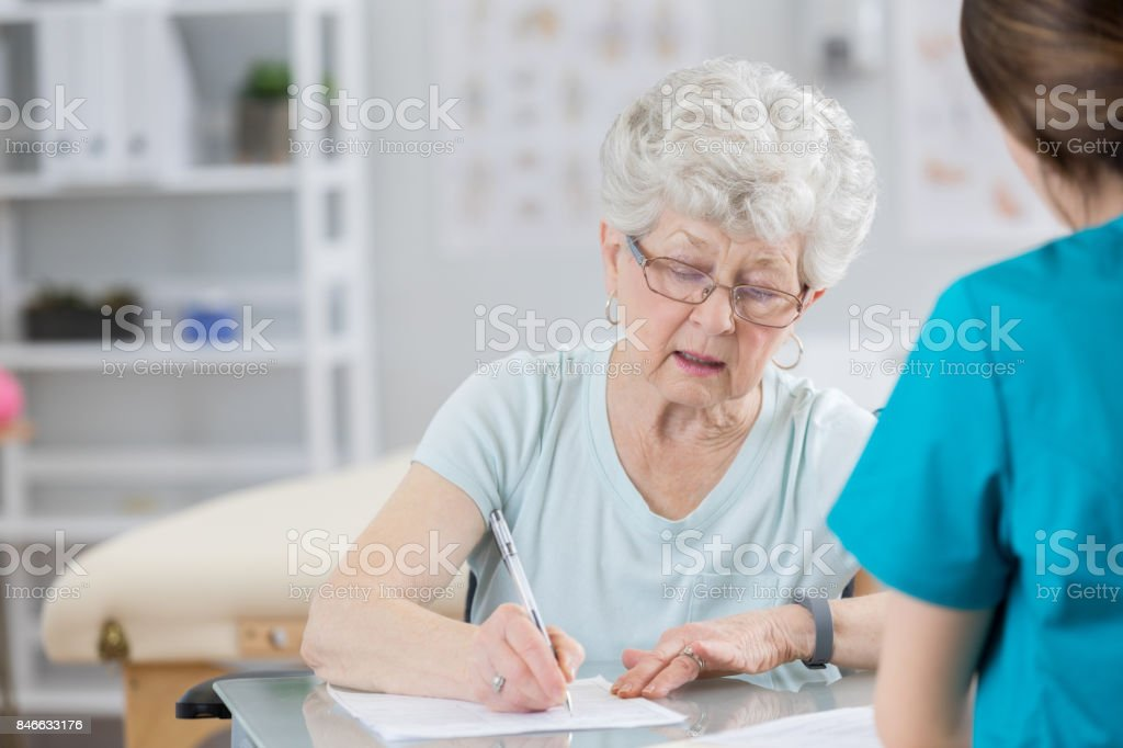 Senior woman concentrates as she fills out insurance or medical...