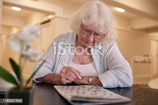 Senior woman sitting alone at a table in a retirement home concentrating on doing the crossword puzzle in a newspaper