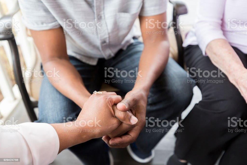 Unrecognizable senior woman holds hands with a senior man. She is...