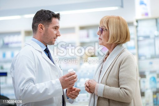 Pharmacist holding pill bottle and giving instructions to a senior woman about using her medicine.