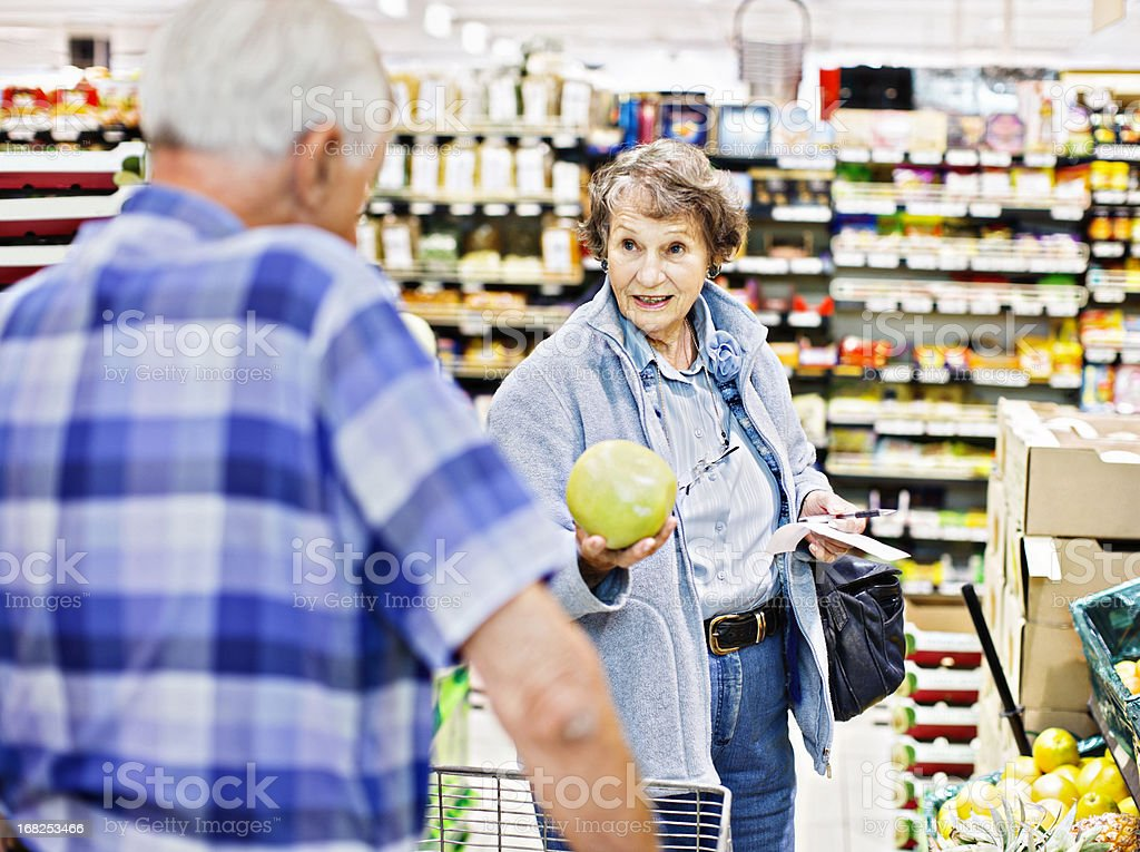 Senior woman consults husband on grapefruit purchase in supermarket stock photo