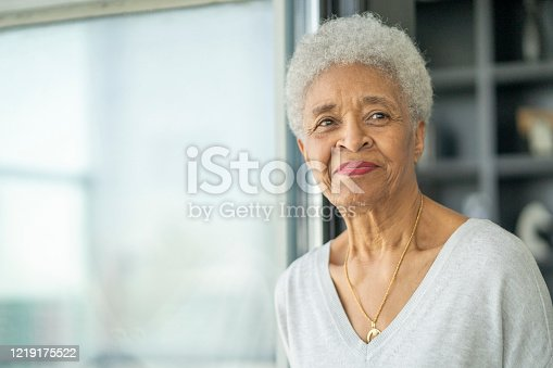 African American Woman looks out the woman as she thinks about life.