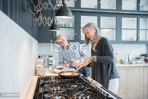 istock Senior woman cooking dinner talking to her husband 513394618