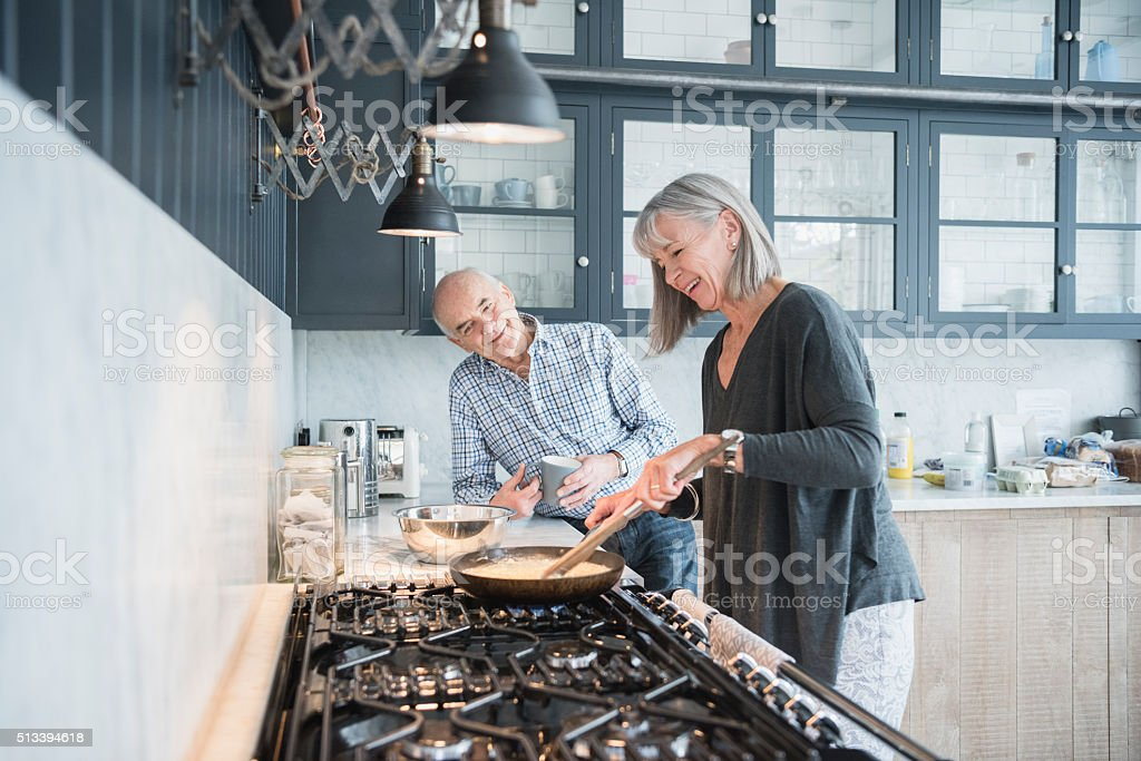 Senior woman cooking dinner talking to her husband stock photo