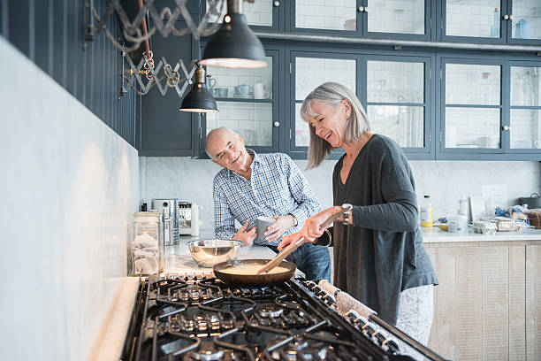 senior woman cooking dinner talking to her husband - home cooking stock photos and pictures