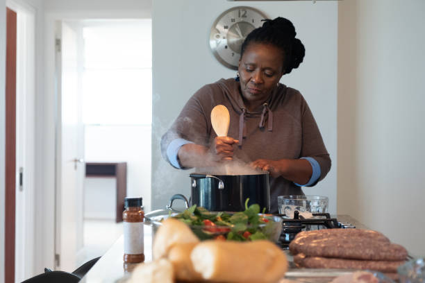 Senior woman cooking food in the kitchen stock photo