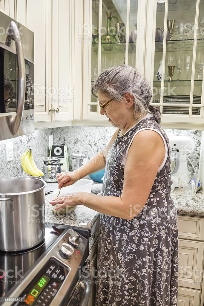 Senior Woman cooking in a beautiful kitchen royalty-free stock photo