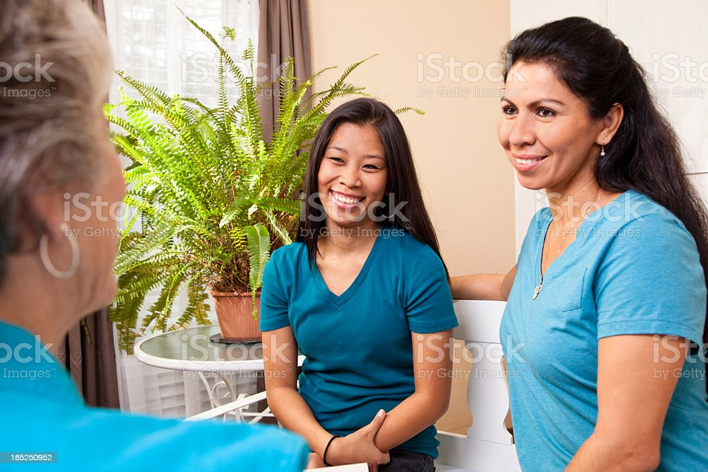 Senior woman counseling younger women on finances and family life. stock photo