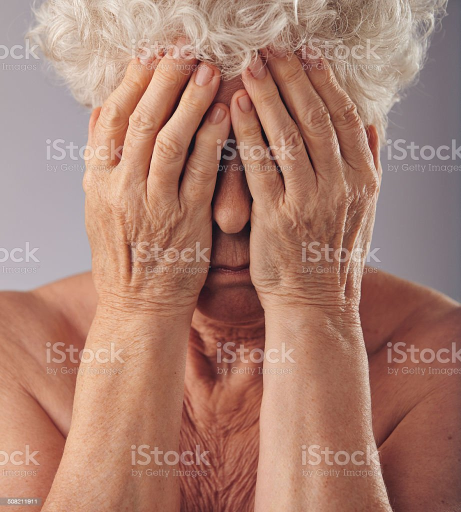 Senior woman covering her face with hands stock photo