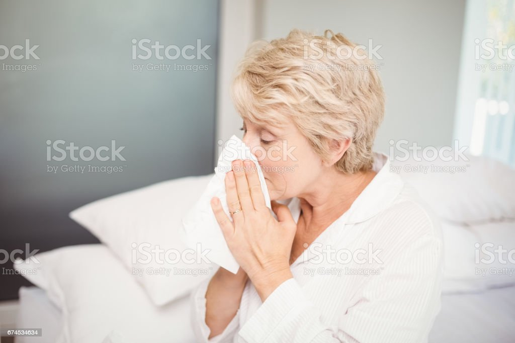 Senior woman covering nose while sneezing at home stock photo