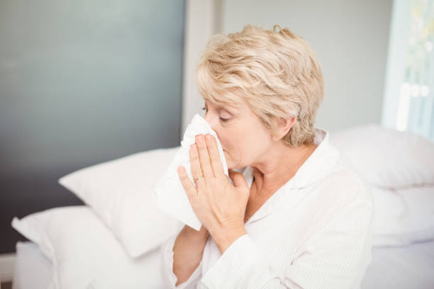Senior woman covering nose while sneezing at home Senior woman covering nose with tissue while sneezing at home human parainfluenza virus stock pictures, royalty-free photos & images