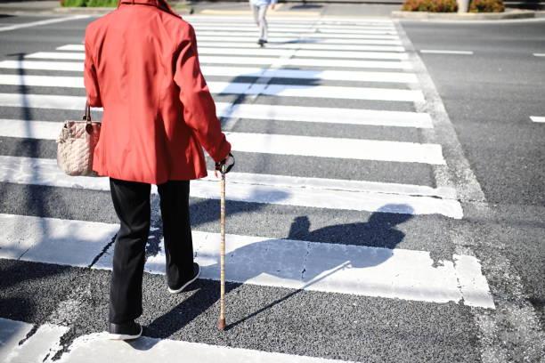 seniorenfrau überquert - fußgänger stock-fotos und bilder