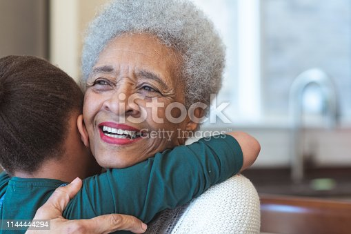 A beautiful senior woman spends time with her granddaughter one afternoon. They are smiling as they embrace each other.