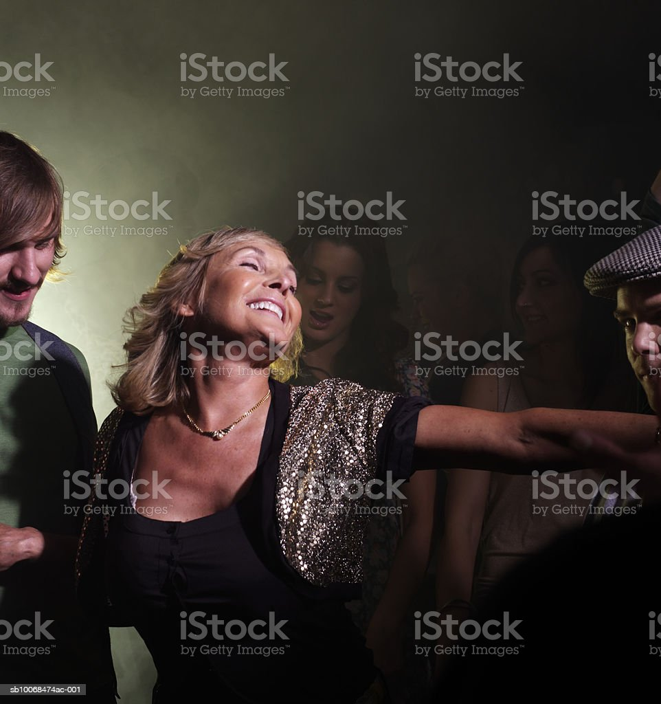 Senior woman dancing with friends in night club 免版稅 stock photo