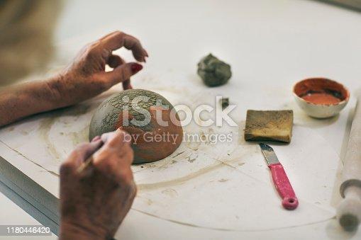627000458istockphoto Senior Woman Decorating Ceramics Bowl At Ceramics Workshop 1180446420