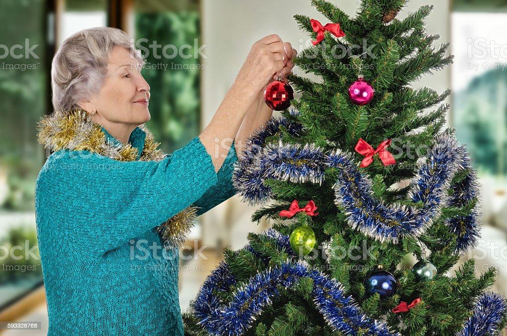 Senior woman decorating Christmas tree stock photo