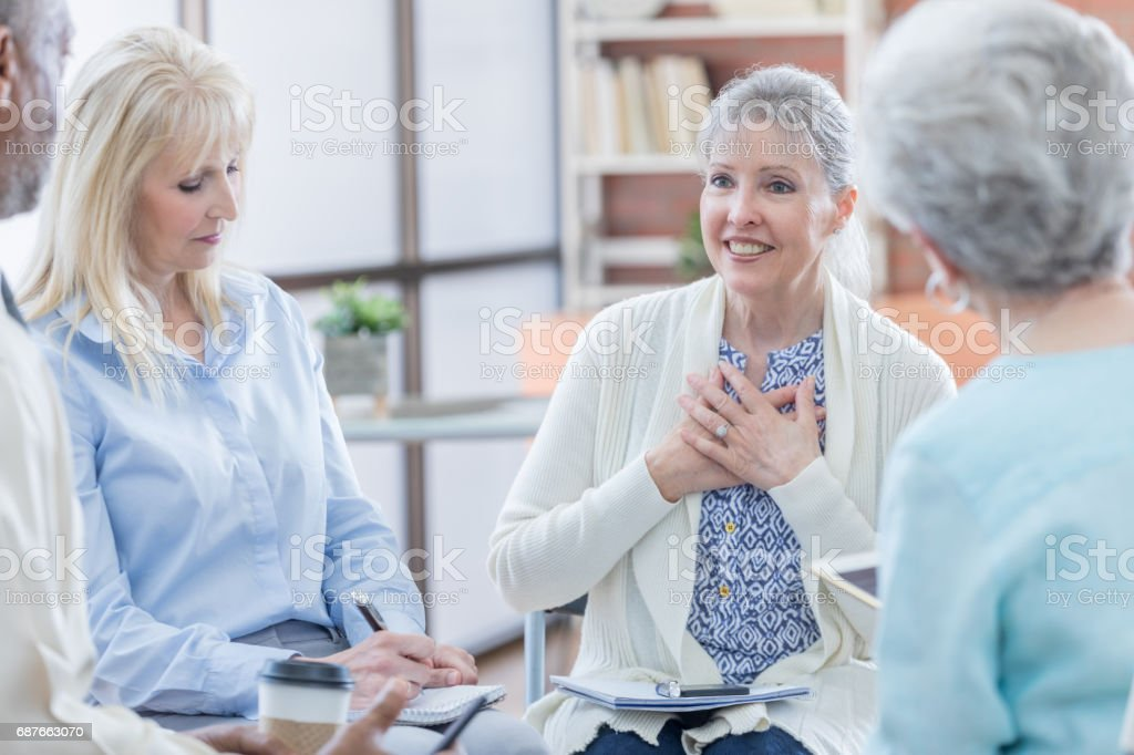 Senior woman discusses her emotions during support group stock photo