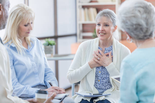 Senior woman discusses her emotions during support group Beautiful senior woman places her hands over her heart while discussing her feelings during a group therapy session with other senior adults. group therapy stock pictures, royalty-free photos & images