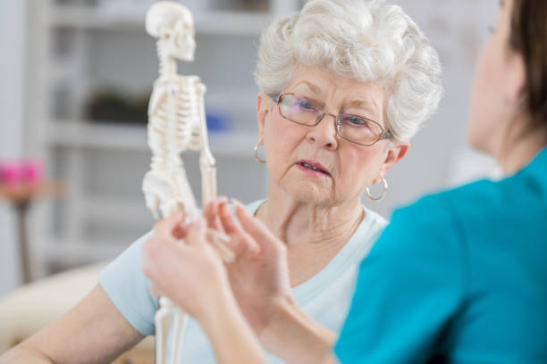 Senior woman discusses posture with physical therapist stock photo
