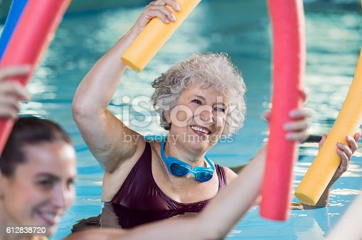 Smiling senior woman doing aqua fitness with swim noodles. Happy mature healthy woman taking fitness classes in aqua aerobics. Healthy old woman holding swim noodles in hand doing aqua gym with young trainer.