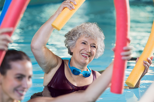 istock Senior woman doing aqua aerobic 612838720
