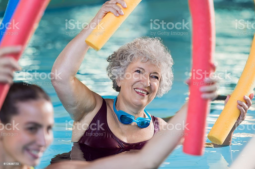 Senior woman doing aqua aerobic - foto de acervo