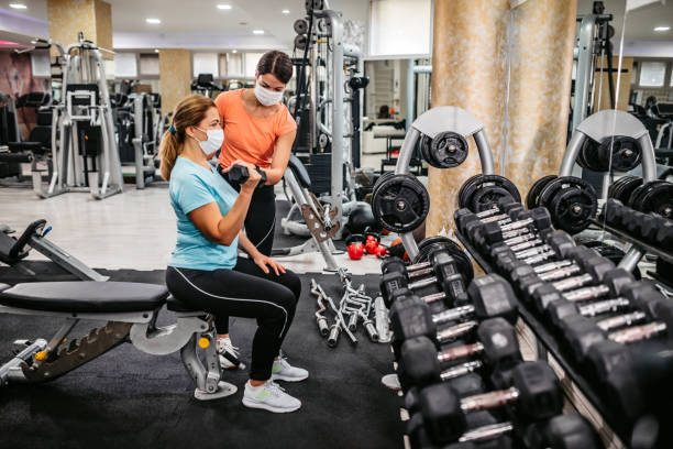 Senior woman doing bicep curls with trainers help stock photo