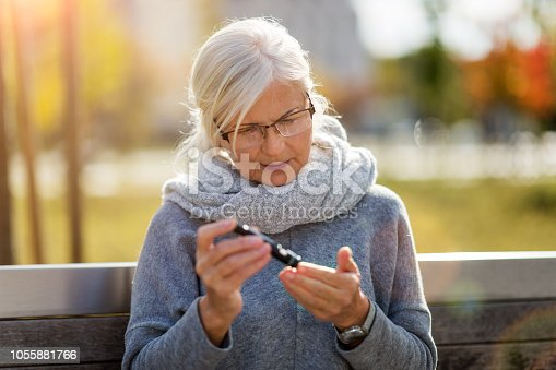 Senior woman doing blood test while sitting on bench