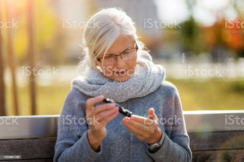 Senior woman doing blood test while sitting on bench stock photo