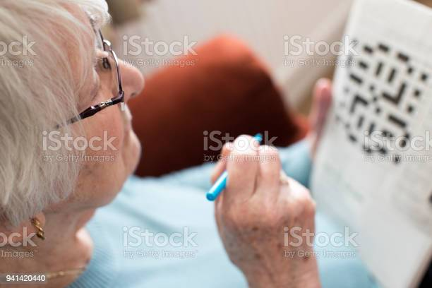 Senior woman doing crossword puzzle at home picture id941420440?b=1&k=6&m=941420440&s=612x612&h=o9e4igeapzytw5tslsf9yop0jp j fckdev2 eqqlb4=