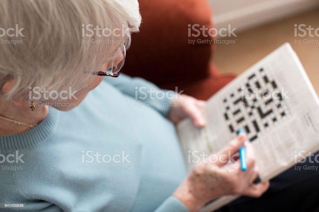 Ältere Frau macht Kreuzworträtsel zu Hause – Foto