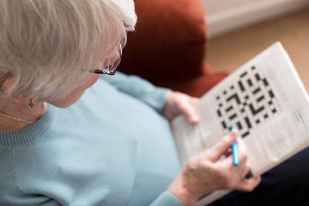 Senior Woman Doing Crossword Puzzle At Home stock photo