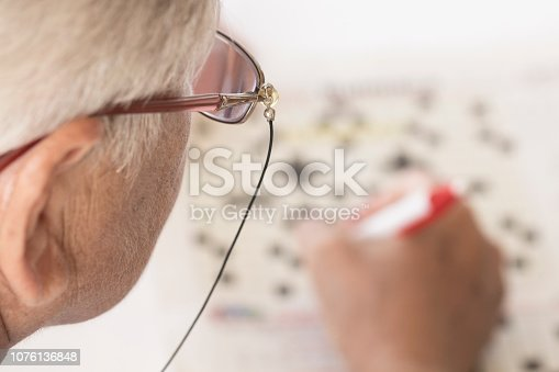 istock Senior Woman Doing Crossword Puzzle 1076136848