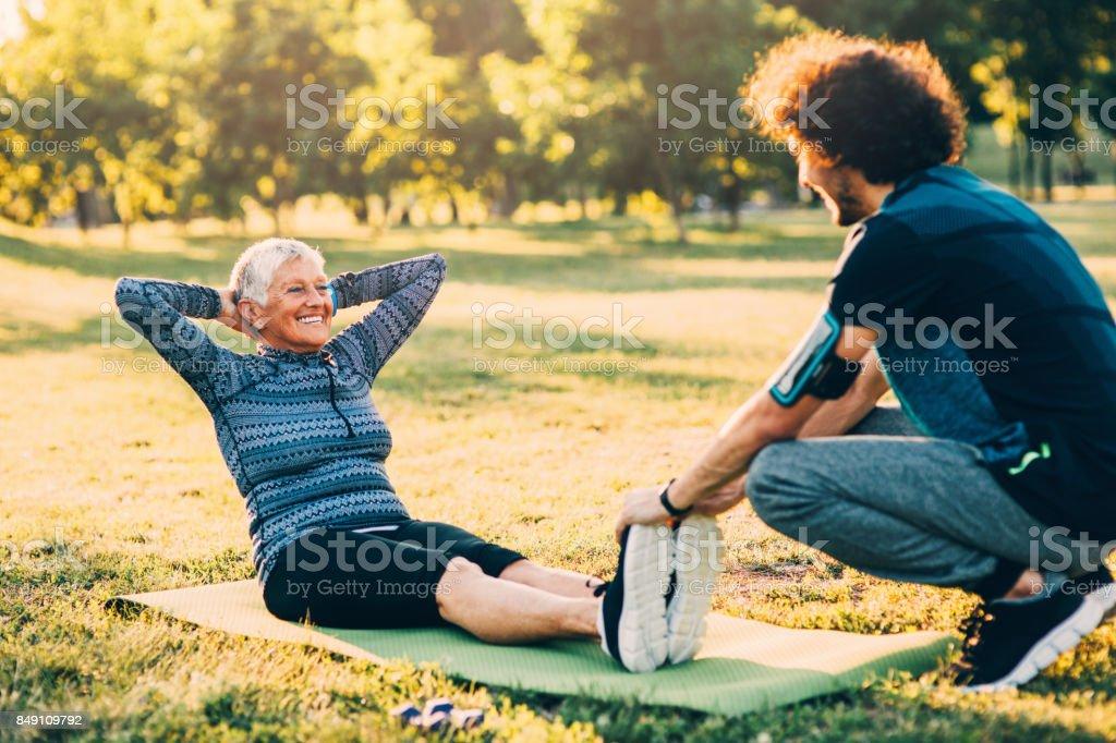 Senior mujer haciendo abdominales con un entrenador personal - foto de stock