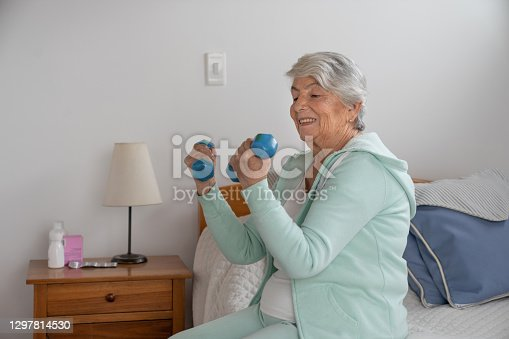 Portrait of a senior Latin American woman doing exercises at home using free-weights - active seniors concepts