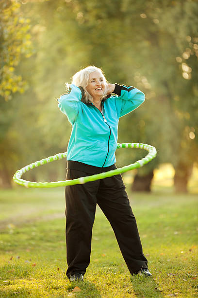 ältere frau, die übungen in der natur - hula hoop workout stock-fotos und bilder