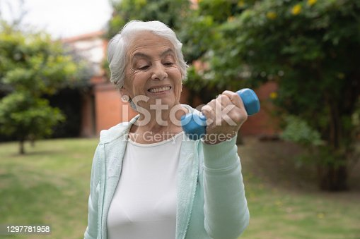 Portrait of a Senior Latin American woman doing exercises outdoors using free-weights and looking very happy – active seniors concepts