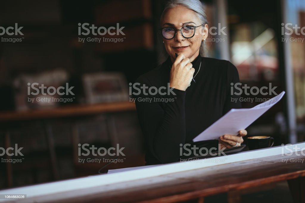 Senior woman doing her work sitting at a coffee shop stock photo