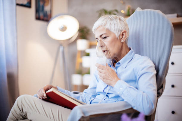 Senior woman doing inhalation and reading book. Portrait of a sick senior woman with grey hair doing inhalation at home and reading book. She is using inhaler for the treatment, inhaling through inhaler mask. smoke inhalation stock pictures, royalty-free photos & images