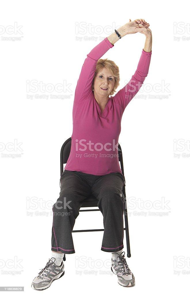 Senior woman doing stretch exercise on chair stock photo
